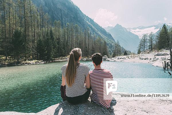 Rückansicht eines jungen Wanderpaares mit Blick auf den Bergsee  Lombardei  Italien