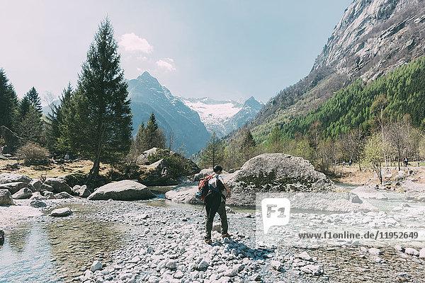 Rückansicht eines am Talfluss stehenden männlichen Felsbrockers  Lombardei  Italien