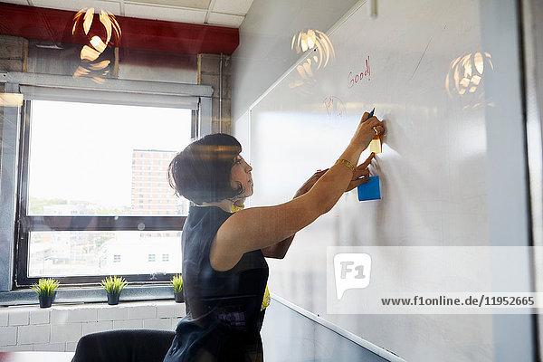 Zwei Frauen im Büro  Brainstorming  Haftnotizen an die Tafel kleben