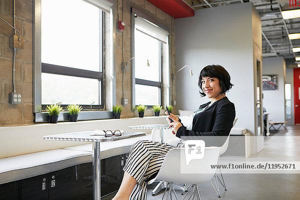 Porträt einer Geschäftsfrau  die in einer Büroumgebung am Tisch sitzt  ein Smartphone in der Hand hält und lächelt