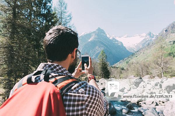 Rückansicht eines männlichen Wanderers beim Fotografieren eines Bergflusses  Lombardei  Italien