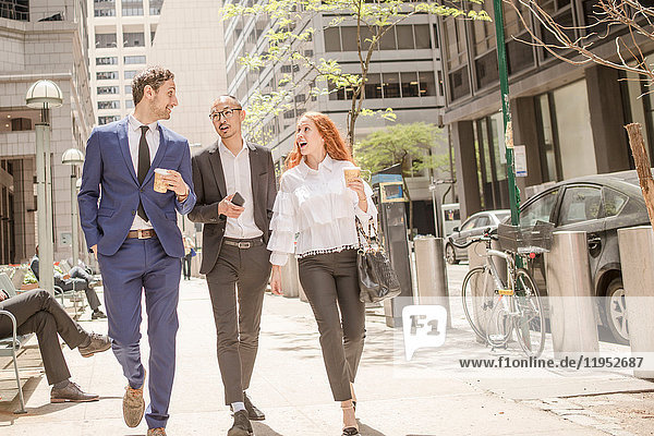 Young businesswoman and businessmen with takeaway coffee strolling along sidewalk  New York  USA
