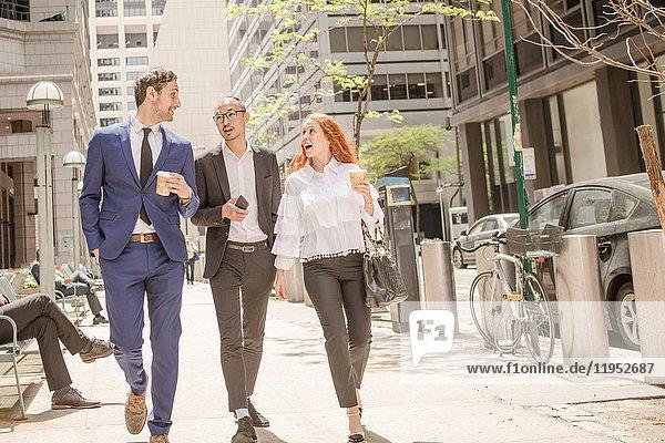 Junge Geschäftsfrau und Geschäftsleute mit Kaffee zum Mitnehmen schlendern über den Bürgersteig  New York  USA