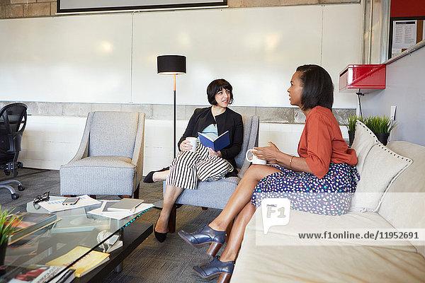 Zwei Geschäftsfrauen sitzen auf bequemen Stühlen im Büro und machen eine Kaffeepause