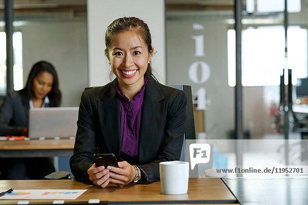Portrait of businesswomen sitting at desk  holding smartphone  smiling