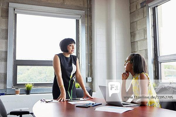 Frau sitzt am Schreibtisch mit Laptop und unterhält sich mit einer Kollegin  die neben dem Schreibtisch steht