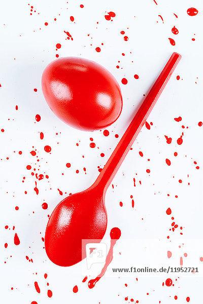 Draufsicht auf rot bemaltes Osterei und Löffel mit Spritzern auf weißem Hintergrund