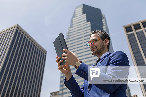 Smiling young businessman looking at digital tablet by New York skyscrapers  USA