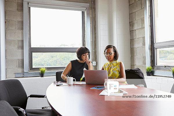 Zwei Frauen sitzen am Tisch im Sitzungssaal und benutzen einen Laptop