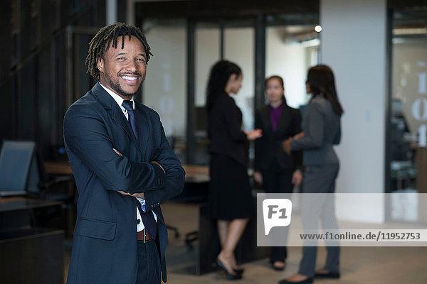 Porträt eines Geschäftsmannes  die Arme verschränkt  lächelnd  im Hintergrund sprechende Geschäftsfrauen