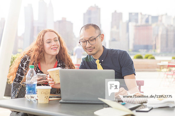 Businessman and woman using laptop at waterfront cafe table  New York  USA