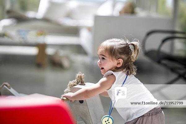 Kleines Mädchen mit Schaukelpferd