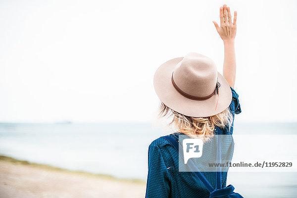 Mittlere erwachsene Frau am Strand stehend  Hand in der Luft  Rückansicht