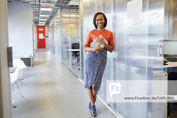 Porträt einer Geschäftsfrau  lehnt sich an Büroumgebung  hält digitales Tablet  lächelt