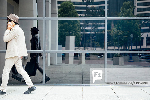 Young man walking past office building  using smartphone
