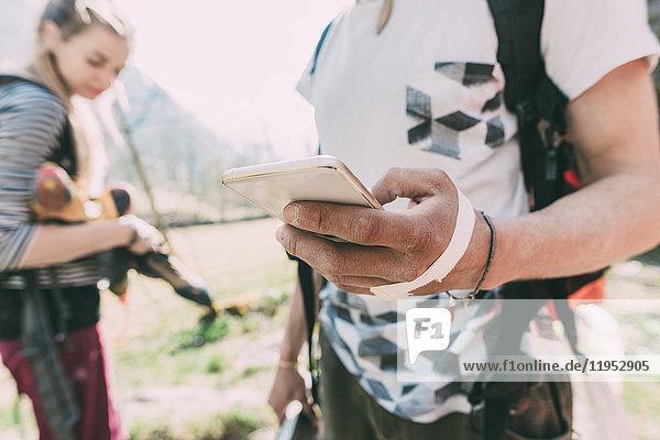 Hand eines männlichen Boulderers  der ein Smartphone hält  Lombardei  Italien