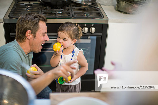 Father laughing at baby girl trying lemon