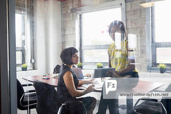 Two women working together in meeting room  brainstorming  using digital tablet