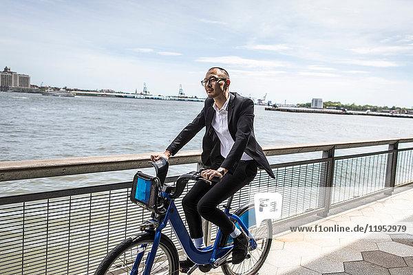 Geschäftsmann mit dem Fahrrad am Wasser  New York  USA