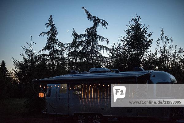 Wohnmobil in ländlicher Umgebung in der Dämmerung  beleuchtet von Lichterketten