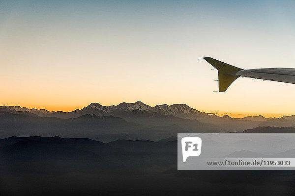 Flugzeugflügel und Luftaufnahme des Sonnenuntergangs über den Bergen  Metropolregion  Chile