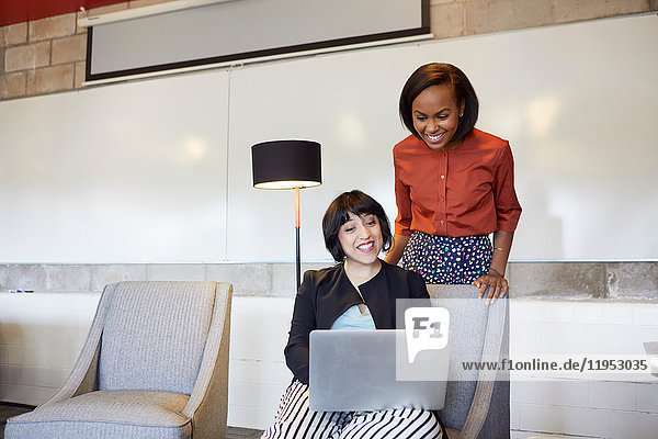 Mid adult woman sitting in chair  using laptop  colleague standing behind her  looking at laptop screen