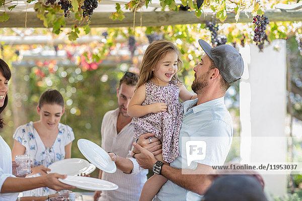 Mann und Mädchen beim Familienessen im Freien
