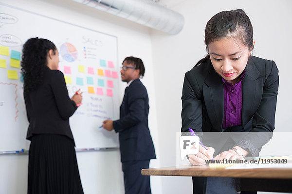 Geschäftsmann und Geschäftsfrauen  im Amt  Brainstorming  Ideen an die Tafel kleben