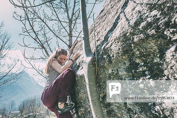 Junge weibliche Bouldererin beim Bouldern  Lombardei  Italien