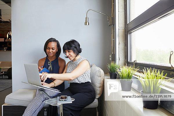 Zwei Frauen sitzen  am Laptop arbeiten  am Laptop-Ständer