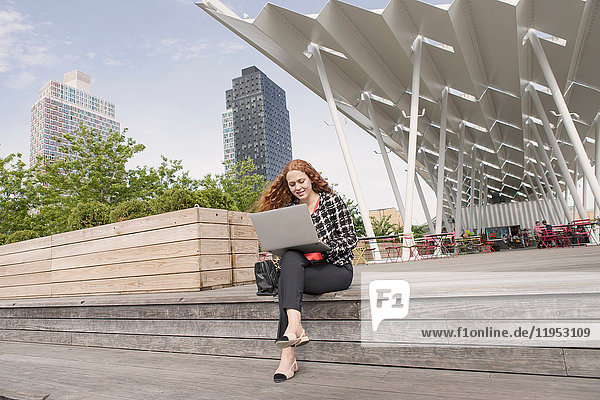 Young businesswoman sitting outside hotel using laptop  New York  USA