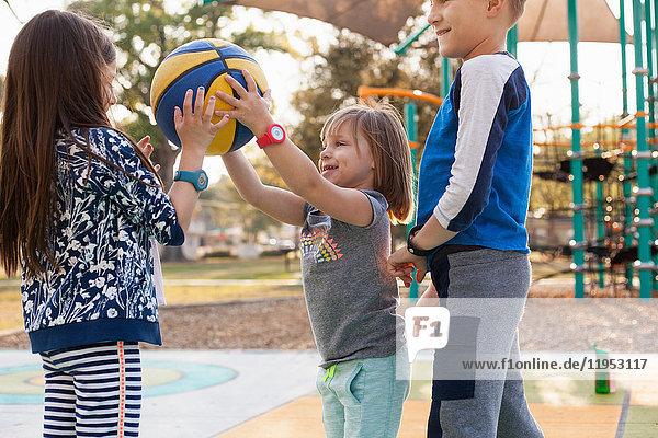 Kinder spielen Basketball auf dem Spielplatz