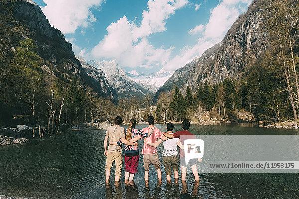 Rückansicht von fünf erwachsenen Freunden knöcheltief im Bergsee  Lombardei  Italien