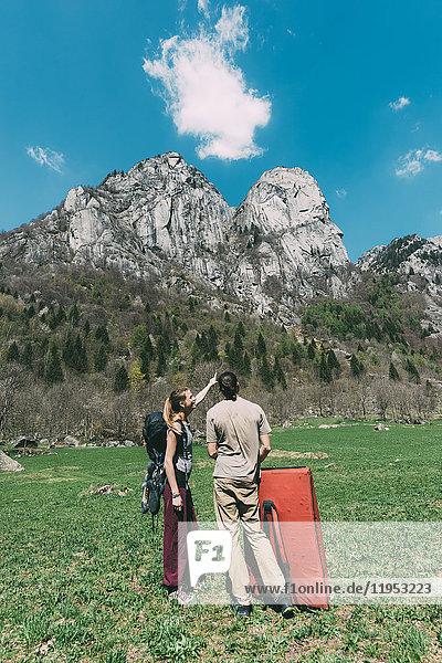 Junge männliche und weibliche Boulderer schauen zum Berg hinauf  Lombardei  Italien