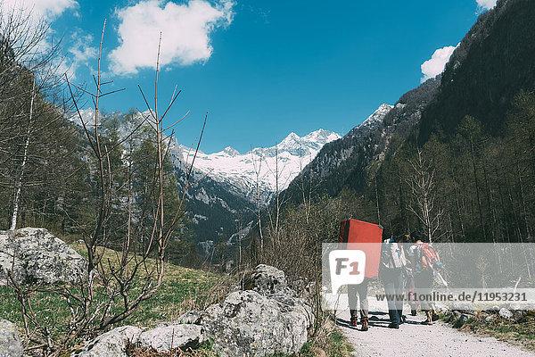 Rückansicht von erwachsenen Freunden mit Bouldermatten-Rucksack beim Wandern entlang einer Landstraße  Lombardei  Italien