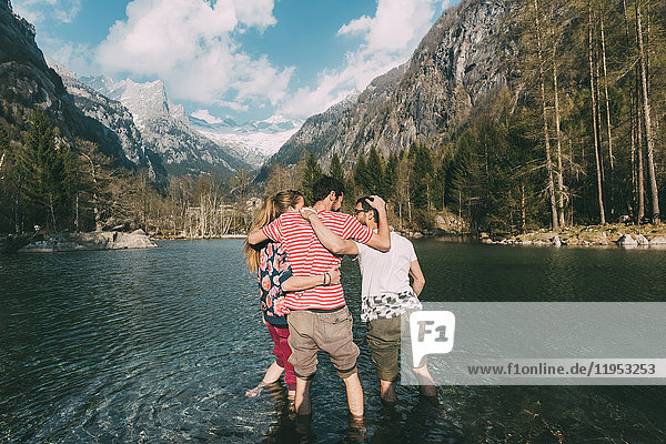 Rear view of three young adult friends ankle deep in mountain lake  Lombardy  Italy