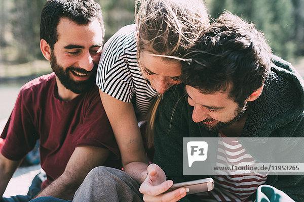 Drei junge erwachsene Freunde schauen und lachen über Smartphone  Lombardei  Italien