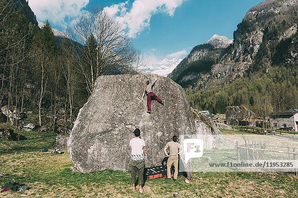 Rückansicht von erwachsenen Boulderfreunden  die einer jungen Frau beim Bouldern zuschauen  Lombardei  Italien