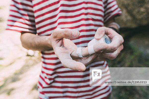 Mittelteil eines männlichen Boulderers  der Klebeband an den Fingern anbringt  Lombardei  Italien