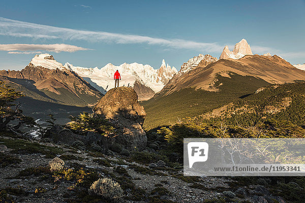Männlicher Wanderer mit Blick auf den Cerro Torre und die Fitz Roy-Gebirgskette im Los Glaciares-Nationalpark  Patagonien  Argentinien