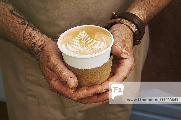 Nahaufnahme eines Mannes mit Tätowierung auf dem Arm  der einen Pappbecher mit Milchkaffee hält.