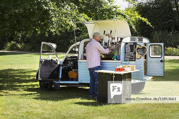 Bärtiger Mann mit Schürze  der an einem blauen mobilen Café steht und Kaffee kocht. Geschäftsinhaber.