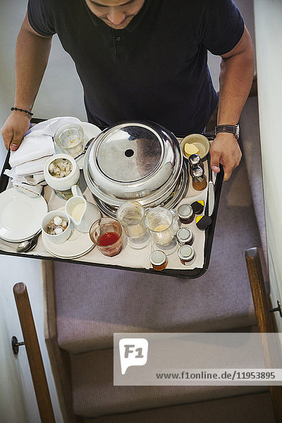 High angle view of man carrying breakfast tray up a staircase.