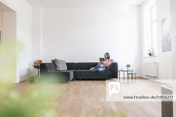 Frau zu Hause mit Tablette auf dem Sofa