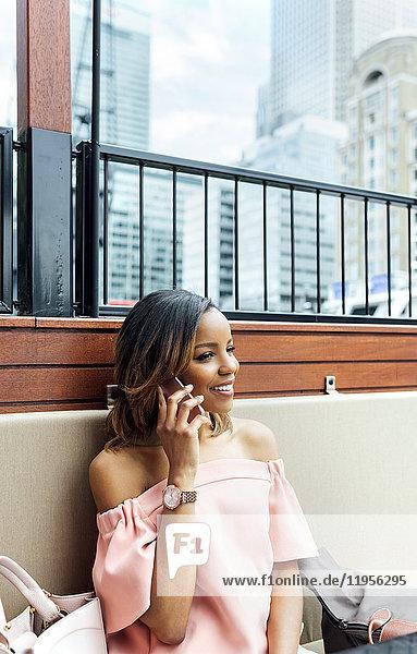 Lächelnde Frau am Telefon in der Stadt