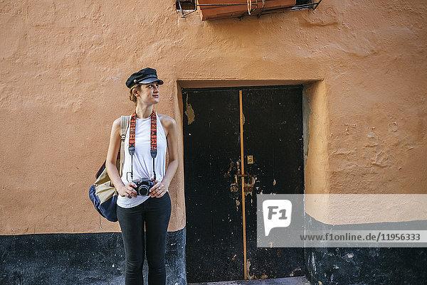 Junge Frau mit Kamera steht vor dem alten Haus