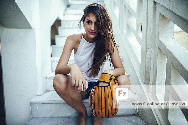 Junge Frau mit Ball und Baseballhandschuh auf der Treppe sitzend