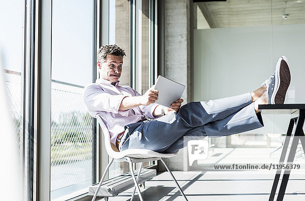Geschäftsmann sitzt mit erhobenen Füßen am Schreibtisch und schaut schockiert auf das digitale Tablett.