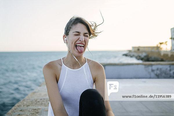 Junge Frau mit Kopfhörern macht lustige Gesichter