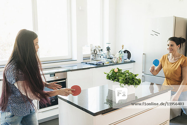 Two women playing table tennis on kitchen counter